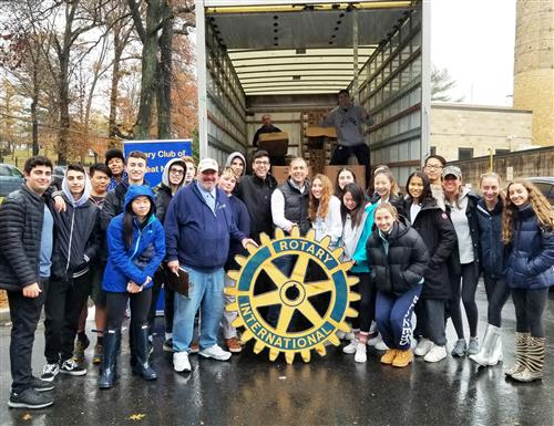 A group of student volunteers stand in front of a delivery truck at the Rotary Club Turkey Drive
