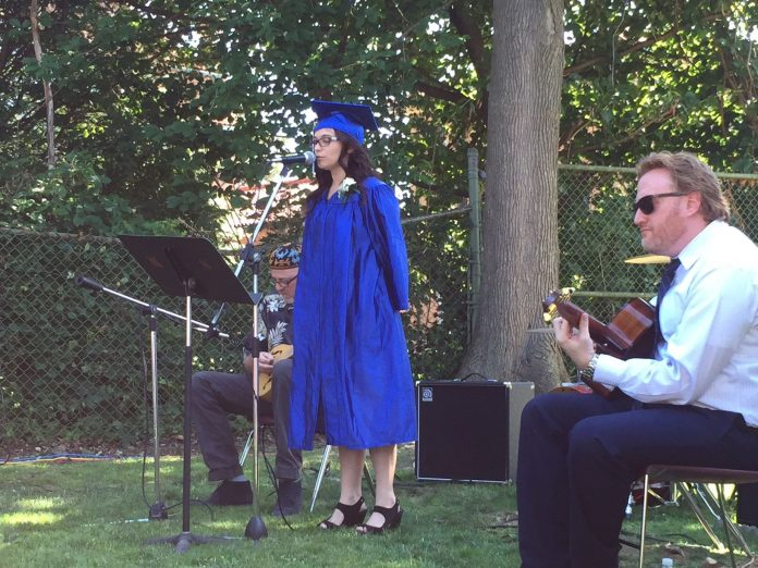 Village senior, in cap and gown, performing ay Village 2015 graduation.